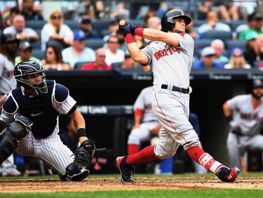 Red Sox left-fielder Andrew Benintendi hits a three-run