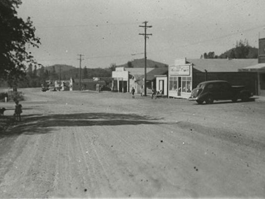 This photograph is looking south from the Summit City School at a row of buildings lining a street in Summit City, circa 1940. An unidentified child with a dog are visible under a tree on the left. Courtesy of Shasta Historical Society.