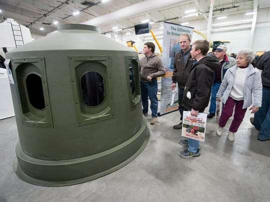 People walk past an Outdoorz Dome hunting blind at the York Farm Show at the Expo Center.The windows open from the inside to shoot.