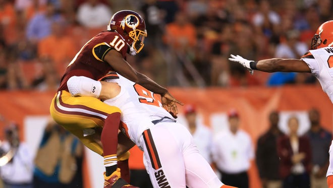 Redskins quarterback Robert Griffin III is tackled by Cleveland Browns defensive end Billy Winn during the first quarter of their preseason game Thursday in Cleveland.