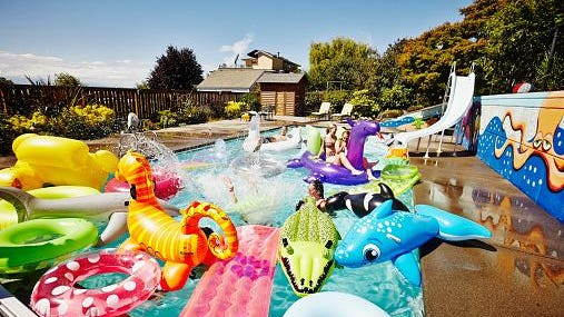 Friends having a pool party with inflatable toys