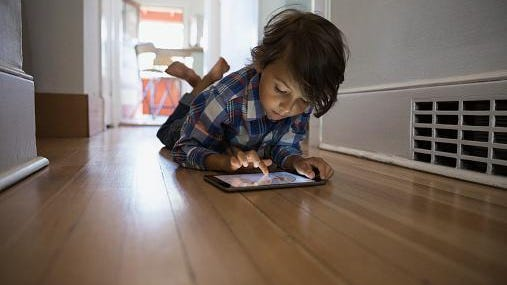 Boy using digital tablet on hallway floor