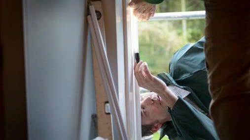 Father and son builders adjusting new window in house, close up