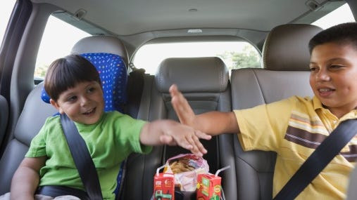 Young boys high-fiving in the backseat