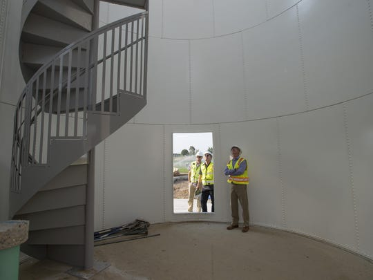City Manager Darin Atteberry looks into a large silo with planning director Kurt Friesen and Craig Kisling at Twin Silo Park near Ziegler Road earlier this week. The 54-acre park, with a community garden and playground, is planned to open in late October.