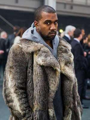 Kanye West poses for photographers at the Givenchy men's Fall-Winter 2014-2015 fashion collection in Paris on Jan. 17.