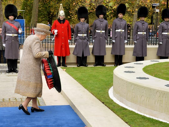 Queen Elizabeth II places a wreath of poppies at the new Flanders Field Memorial outside the Guards Chapel on Nov. 6, 2014, in London, England.