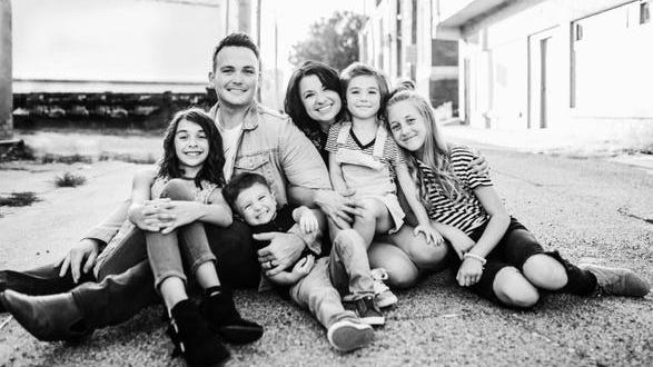 Roxy Taylor, in the middle, is surrounded by her family including her husband Chase and their children, Nevaeh, Autumn, Daisy, and Shepherd