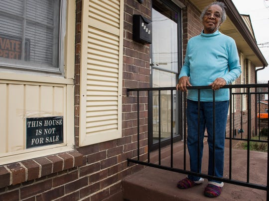 Sallie Dowell stands on her porch at her Southside