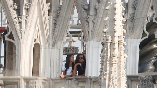 U.S. first lady Michelle Obama and her daughter Malia watch the panorama from the roof of the Duomo gothic cathedral in Milan, Italy, Thursday, June 18, 2015.