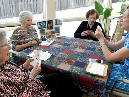 Stephanie Freudenthal, Edith Hudson, Emma Schwaber and Edith's daughter, Chris Follansbee, plays bridge together at Abe's Garden, a local memory care facility on June 19, 2018.