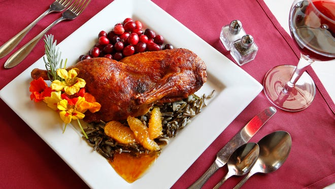 A half duck served with wild rice and cranberries.
