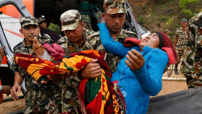 A victim with a broken leg from Saturday's massive earthquake, is carried by Nepalese soldiers as she arrives by helicopter from the heavily-damaged Ranachour village at a landing zone in the town of Gorkha, Nepal, Tuesday, April 28, 2015. Helicopters crisscrossed the skies above the high mountains of Gorkha district on Tuesday near the epicenter of the weekend earthquake, ferrying the injured to clinics, and taking emergency supplies back to remote villages devastated by the disaster. (AP Photo/Wally Santana)