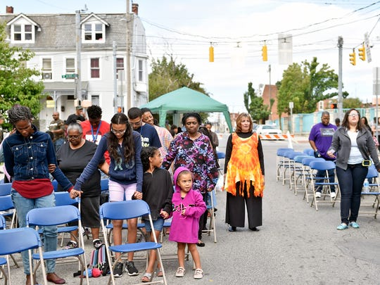 Sisters Zuri Jackson, 8, and Ari Jackson, 3, center, hold hands during a period of prayer at the Love Over War Fest hosted by New Covenant Community Church Saturday on South West Street in York. The block party featured performances and food.