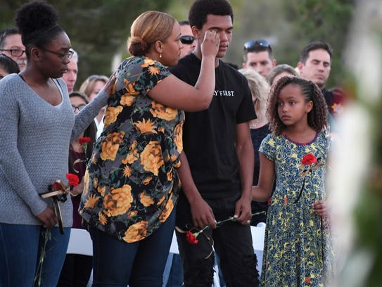 Veronica Hartfield wipes a tear from her son, Isaiah,