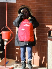"""Salvation Army bell ringer Anna Diamond belts out a rendition of """"The Twelve Days of Christmas"""" Tuesday, Dec. 12, 2017, outside Kroger on Lansing's west side while collecting donations."""