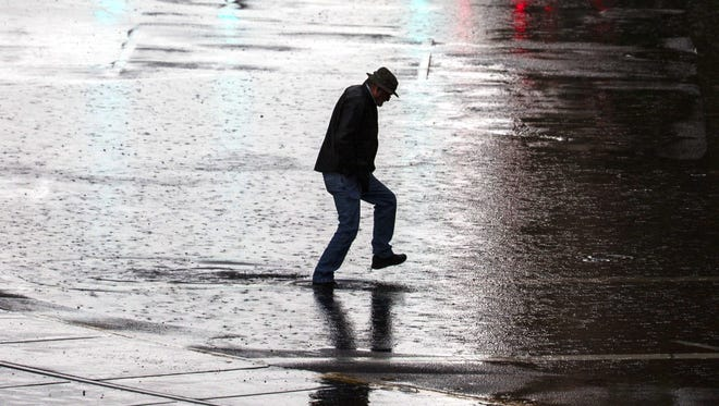 A man crosses a large puddle as El Nino hits downtown Phoenix near city scape on Jan. 7, 2016 in Phoenix, Ariz.