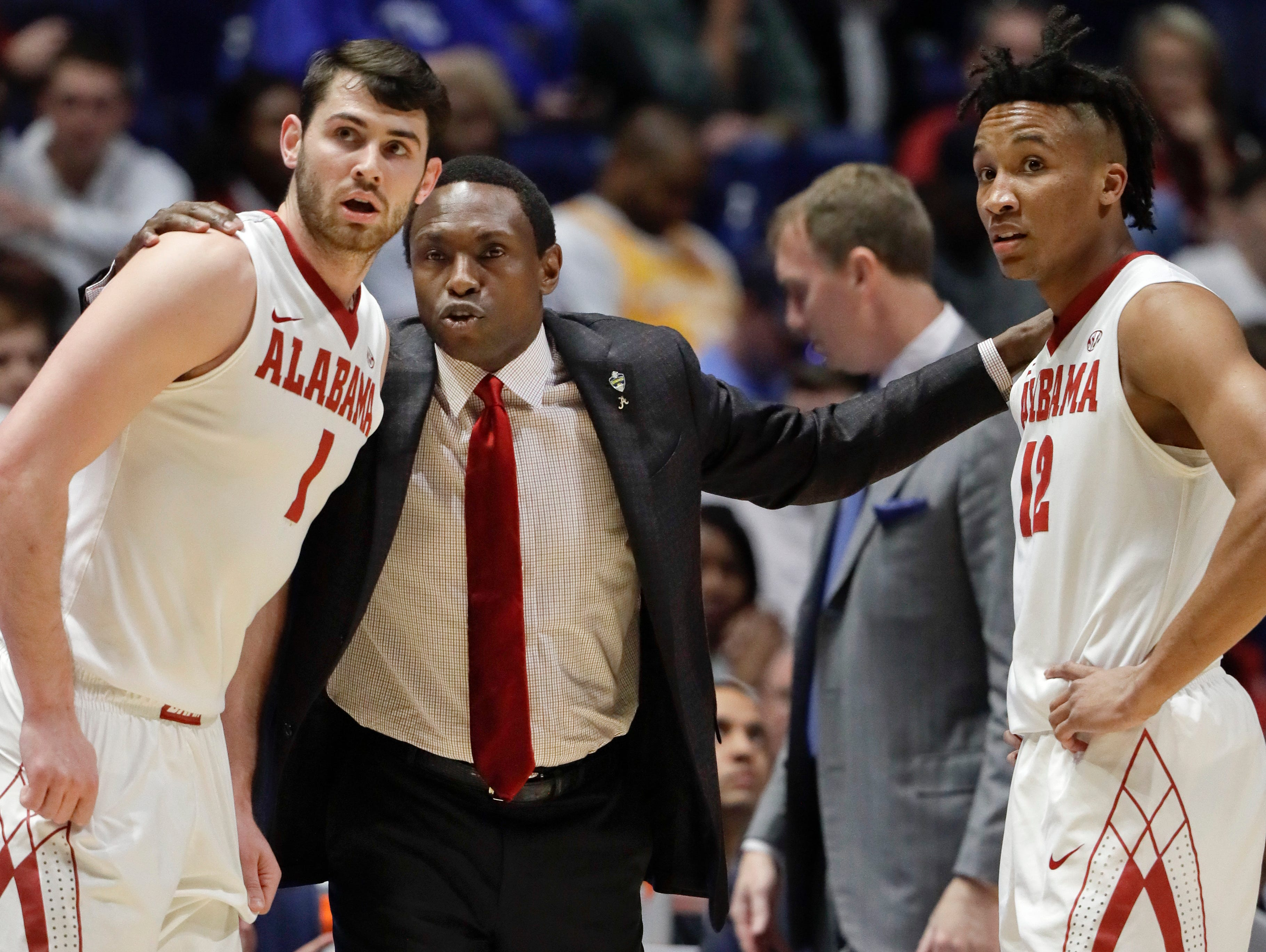 Alabama head coach Avery Johnson, second from left, talks with Riley Norris (1) and Dazon Ingram (12) during the first half of an NCAA college basketball game against Mississippi State at the Southeastern Conference tournament Thursday, March 9, 2017, in Nashville, Tenn.