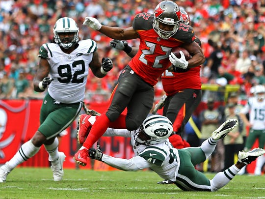 Tampa Bay Buccaneers running back Doug Martin leaps over New York Jets cornerback Buster Skrine in the second half at Raymond James Stadium.