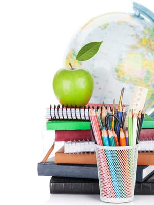 School and office supplies. Notepads, colorful pencils, apple and globe. Isolated on white background.