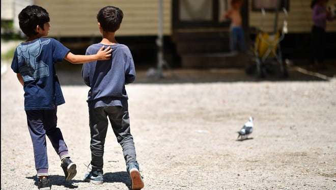 """Two boys, members of the Roma community, walk at the """"River Village"""" Roma camp, managed by the Onlus Isola Verde association on June 19, 2018, on the outskirts of Rome."""