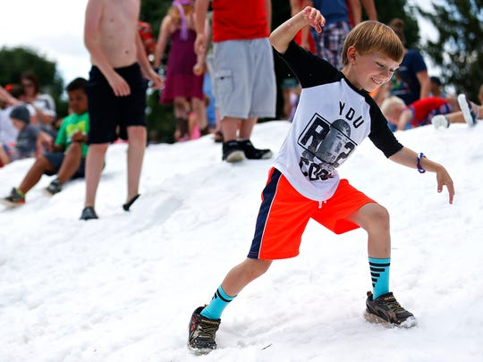 A child plays in a mound of snow during this year's Snowfest at Jordan Valley Park in Springfield, Mo. on June 25, 2016.