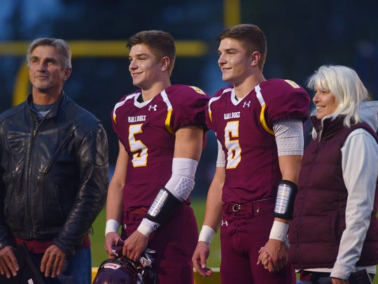 Jadon Janke (5) and Jaxon Janke (6) stand with their parents before the game against Tea Area Friday, Oct. 6, at Trojan Field. The players celebrated seniors night.