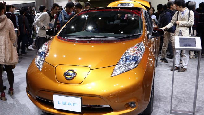 "Japanese auto giant Nissan Motor's electric vehicle ""Leaf"" is seen on display at the Tokyo Motor Show on November 2, 2015. Nissan boosted its full-year forecasts, citing new model rollouts along with upbeat sales in North America and Europe that offset weakness in the home market on November 2. T"