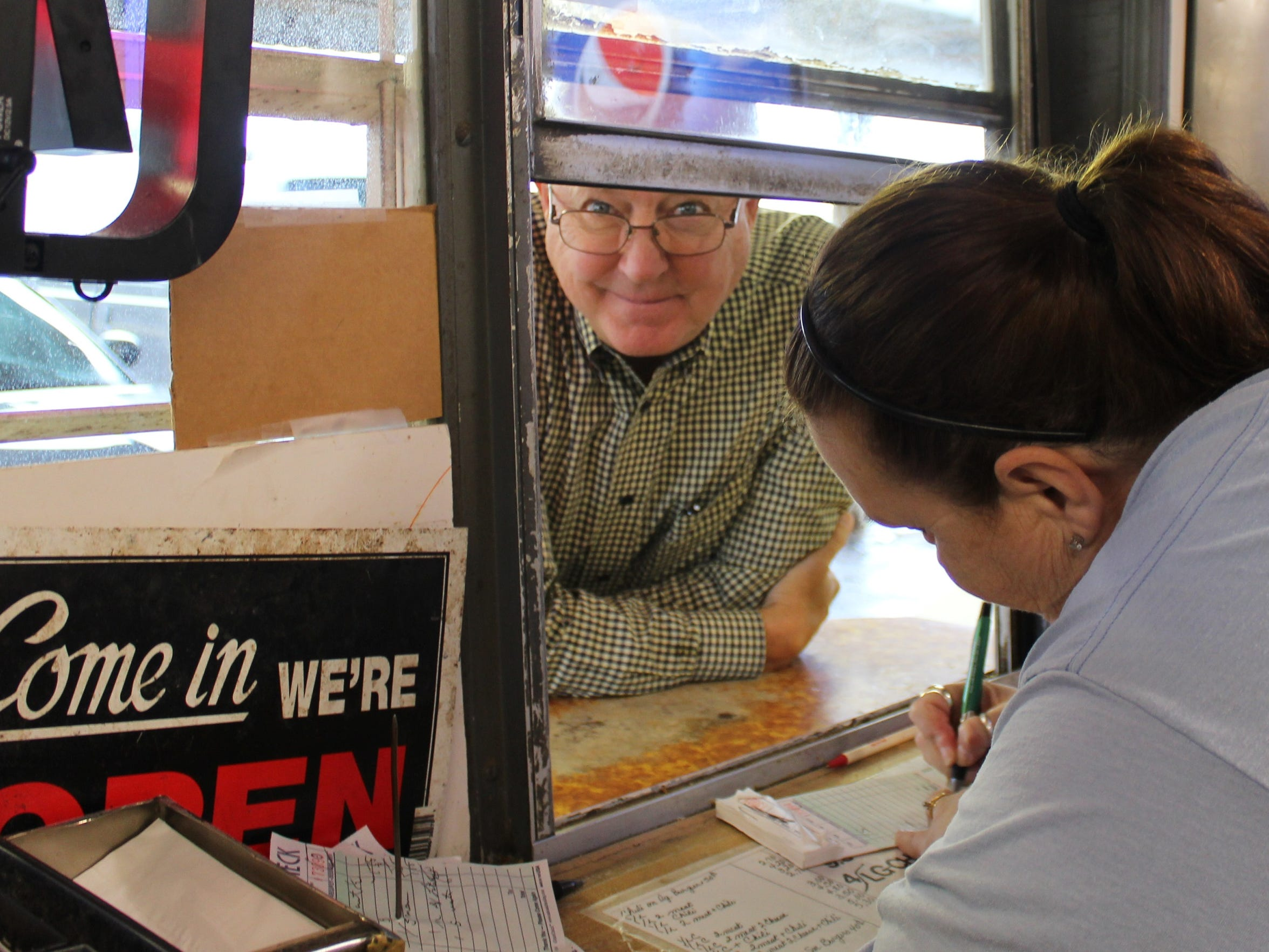 Kelly Yates takes a customer's order at one of two service windows at Larry's Better Burger. Her customer is all smiles thinking about what's for lunch. Many customers come to Larry's every week; a few, the owner said, come every day.