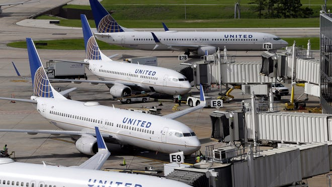 In this July 8, 2015, photo, United Airlines planes are parked at their gates as another plane, top, taxis past them at George Bush Intercontinental Airport in Houston.