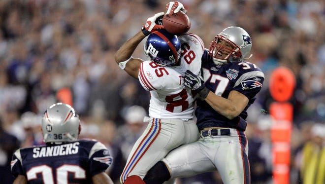 FILE - In this Feb. 3, 2008, file photo, New York Giants receiver David Tyree (85) catches a pass while in the clutches of New England Patriots safety Rodney Harrison (37) as James Sanders (36) watches during the fourth quarter of the Super Bowl XLII football game in Glendale, Ariz. A win Sunday night, Feb 1, against the Seattle Seahawks would even the Patriots record in Super Bowls at University of Phoenix Stadium at 1-1. New England is seeking a championship, not closure for its 17-14 loss to the New York Giants in 2008.