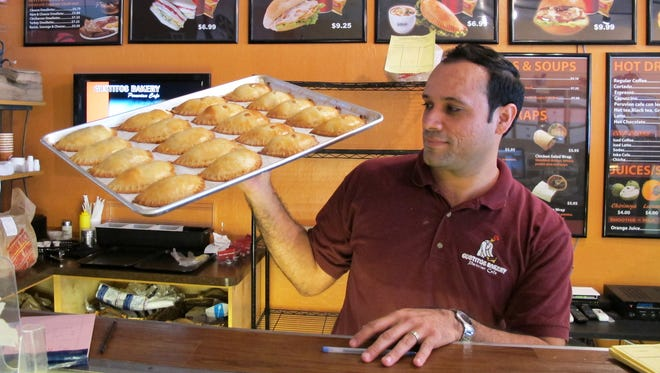 Gustitos Bakery Cafe co-owner Gonzalo Torres carries a tray of freshly baked empanadas Feb. 8, 2017, at Gustitos' original location at 5417 Airport-Pulling Road in North Naples.
