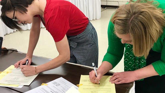 Teresa Schreiner (left) and Kim Skornogoski swear and sign documents to officially become members of the Great Falls Public Schools Board of Trustees. Schreiner and Skornogoski were selected by voters in the May 8, 2018 election.