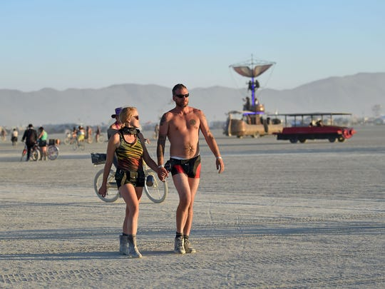 Robin Hertz, left, and Van Anderson take a walk on the playa at Burning Man on August 28, 2017. This year's Burning Man theme is Radical Ritual.