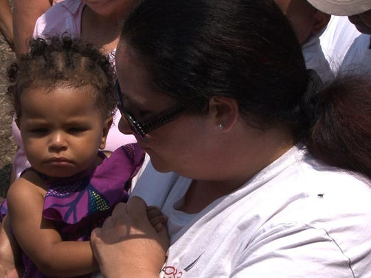 Danielle Murphy holds her 1-year-old niece, Neveah, at a tribute Sunday to the baby's mother, Jamie Murphy, who was found dead Thursday in Canby Park.