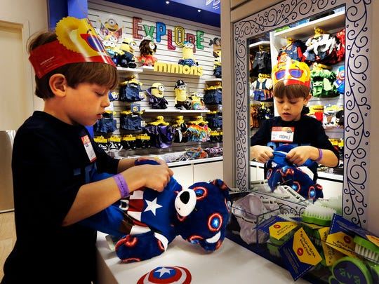 Landon Penovich dresses the bear he built during the grand opening of a Build-A-Bear Workshop.  Build-A-Bear has a permit for a new store on Fort Campbell Boulevard.