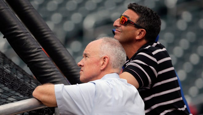 FILE - In this Aug. 10, 2015, file photo, New York Mets general manager Sandy Alderson, left, and his special assistant, J.P. Ricciardi, watch batting practice before a baseball game between the Colorado Rockies and the Mets, in New York. With the Mets sinking fast toward the bottom of the National League standings, baseball operations were turned over Tuesday, June 26, 2018, to a trio of Alderson's assistants when the general manager made the announcement that he was stepping down because his cancer has returned. John Ricco, Ricciardi and Omar Minaya have decades of front office experience among them, both in New York and elsewhere around the majors.