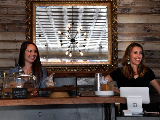 Sisters-in-law Molly (left) and Michelle Bellah laugh as they work the counter at Stomping Grounds Coffee & Tea Co. on Firday in Throckmorton. The women said their donation-only strategy has allowed them to thrive by being able to donate money from proceeds to Harvey relief groups and more local causes.