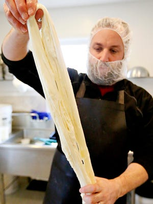 Director of Cheese Cultures Wade Smith smoothes out about four pounds of curds by stretching them into smooth provola at Caputo Brothers Creamery farmhouse in Spring Grove, Pa. on Tuesday, Jan. 12, 2016. (Dawn J. Sagert - The York Dispatch)