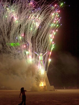 """BURNINGMAN --  A participant watches """"The Man"""" go up during the Burning Man festival in the Black Rock desert of Nevada."""
