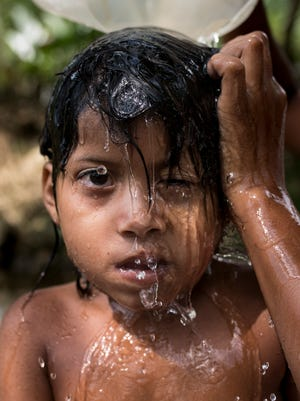 A child from the La Cadena village bathe in a small creek. A major issue for this community is water contamination fecal matter and pesticides from the nearby palm oil agriculture industry. April 2, 2017