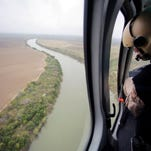 A U.S. Customs and Border Protection Air and Marine agent looks out along the Rio Grande on the Texas-Mexico border, Tuesday, in Rio Grande City, Texas.