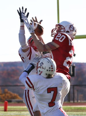 Devon Caruso from Morris Hills jumps above Governor Livingston defenders Pat DeAngelis and David Vill to catch a pass and the score the Scarlet Knights' third touchdown in the first round of the NJSIAA North 2, Group III football playoffs at Morris Hills High School on Saturday.