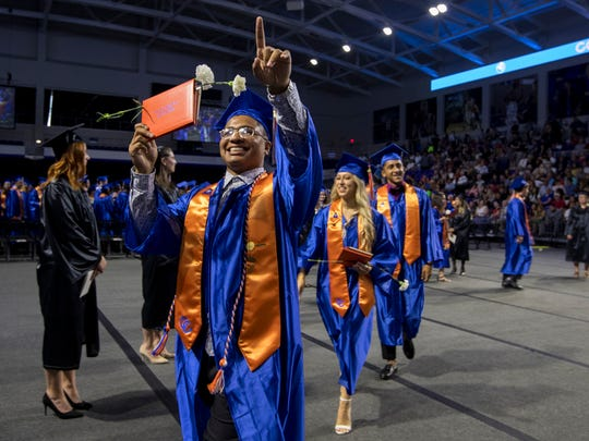 Cape Coral High School senior Juan Milan, 19, points to the crowd in celebration after the completion of his graduation ceremonies Saturday, May 19, at Suncoast Credit Union Arena in Fort Myers.