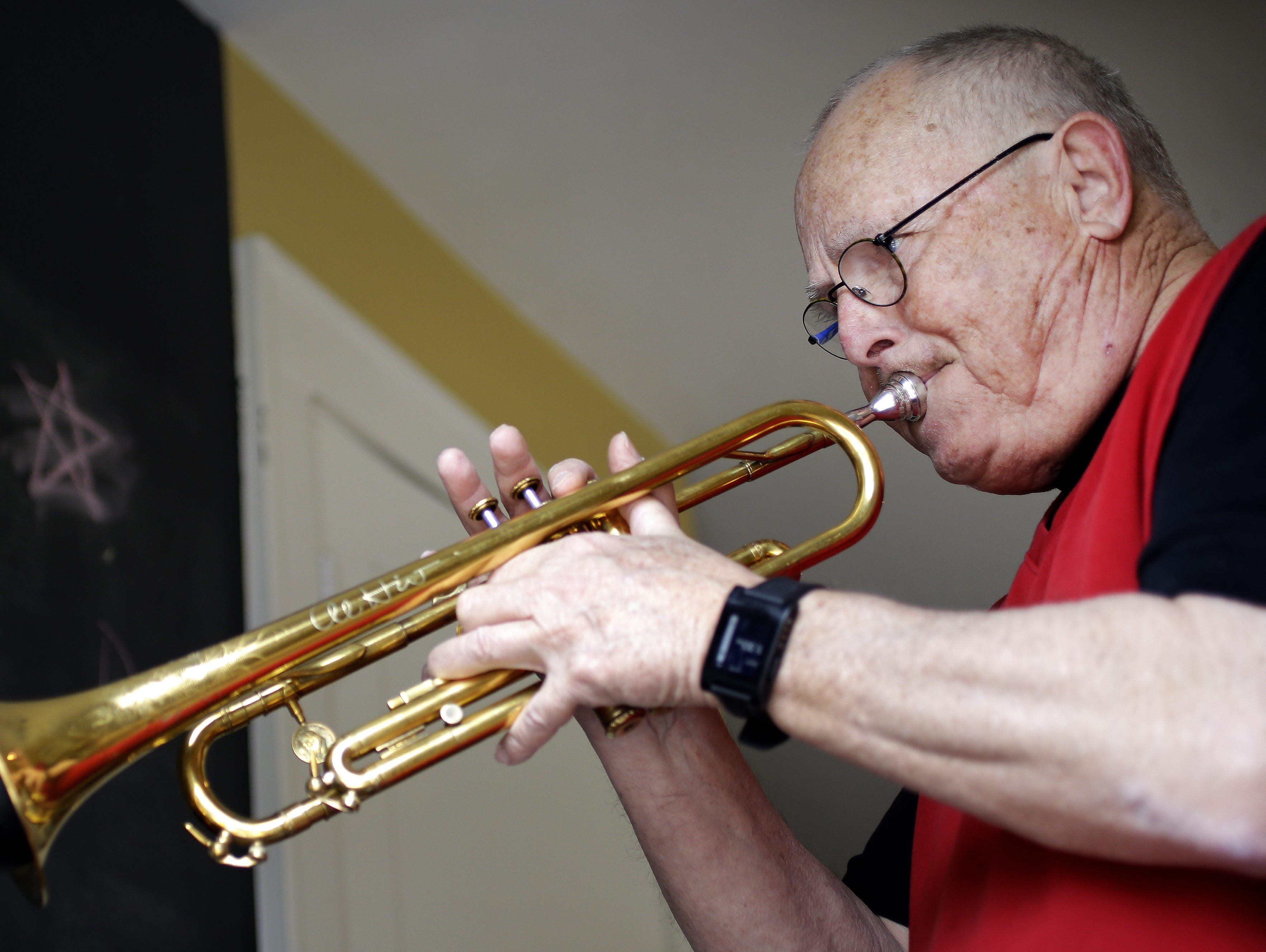 Clyde Peach plays the trumpet inside his kitchen studio on April 6, 2016. Peach plays and produces the background music for his business' YouTube videos.
