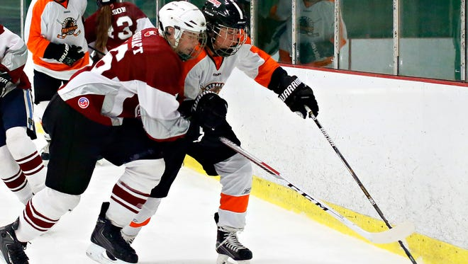 Manheim Central's Isaac Dorwart, left, and Central York's Thomas Knapp struggle to control the puck during ice hockey action at York City Ice Arena in York City, Monday, Dec. 5, 2016. Central York would win the game 10-0. Dawn J. Sagert photo