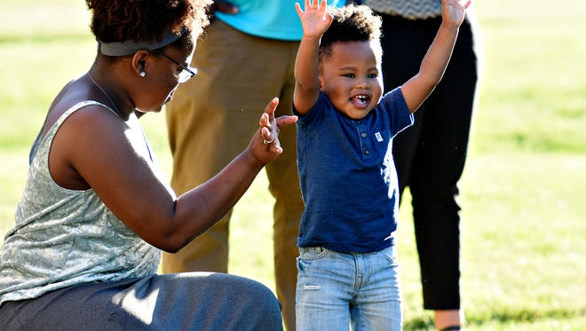 Jenell Brown, of Manchester Township, does yoga with her son Micah Brown, 2,  led by Kent Nazereth during a Yoga break on the first day of the inaugural Gusa World Music Festival at Foundary Park in York City, Friday, June 15, 2018. Dawn J. Sagert photo