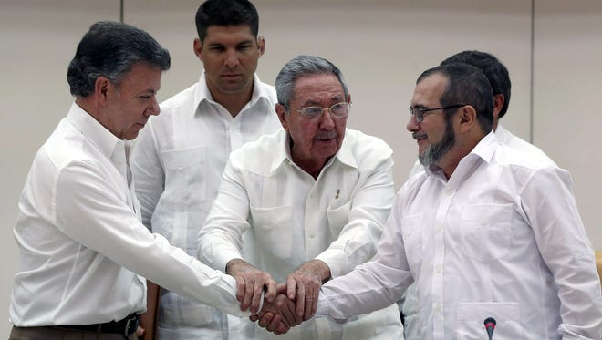 """Cuban President Raul Castro, center, holds hands with Colombian President Juan Manuel Santos, left, and leader of the Revolutionary Armed Forces of Colombia (FARC) Timoleón Jiménez, known as """"Timochenko,"""" during a news conference announcing an agreement between the two parts in Havana on Sept. 23, 2015."""