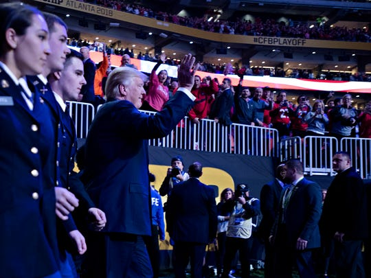 President Donald Trump waives while standing on the field before the NCAA National Championship football game between Alabama and Georgia on Monday, Jan. 8, 2018, in Atlanta, Ga.