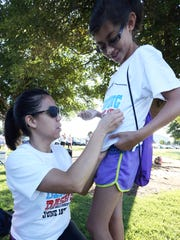 Laura Suarez pins a race registration number on daughter Isabel Suarez before the start of the second annual Denning Dash on June 18 at Eastwood Park.